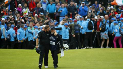 Portrush, Northern Ireland, 21 July: Ireland's Shane Lowry, assured of victory at the 148th Open Championship, shares a congratulatory hug with his caddie Brian Martin as they walk up the 18th fairway at Royal Portrush Golf Club. (Photo by Kevin C. Cox/Getty Images)