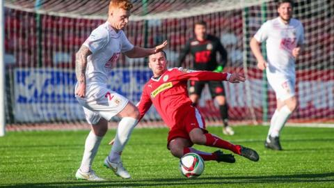 Ports defender Chris Casement is tackled by Cliftonville winger Martin Donnelly