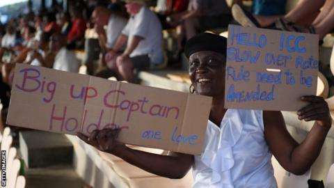 A fan holds up a sign in support of Jason Holder