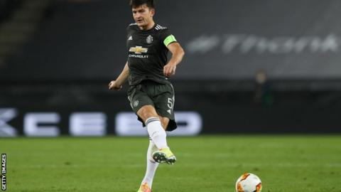Harry Maguire kicks the ball while playing for Manchester United