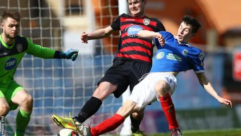 Coleraine's Adam Mullan is challenged by Stephen Fallon during his loan spell at Linfield