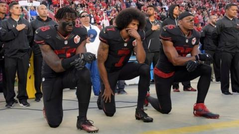 San Francisco 49ers outside linebacker Eli Harold (58), quarterback Colin Kaepernick (7) and free safety Eric Reid (35) kneel during the US national anthem