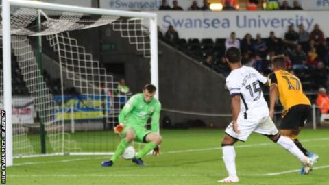 Wayne Routledge shoots through the legs of Cambridge goalkeeper Callum Burton to score Swansea's sixth goal
