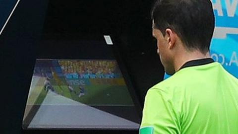 A referee uses VAR at the World Cup