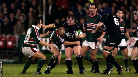 Andrew Millward of Neath is tackled by Neil Back of Leicester during the Heineken Cup match between Neath and Leicester Tigers at The Gnoll on October 11, 2002.