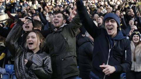 Oxford fans celebrate beating Swansea City in the FA Cup