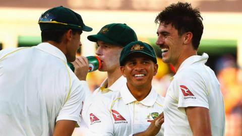 Australia celebrate a wicket by Pat Cummins (right)