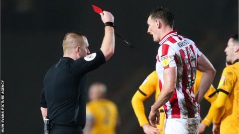 Will Boyle of Cheltenham Town is shown a red card by referee Lee Swabey after bringing down Jamille Matt
