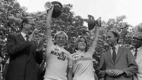 1984 Tour de France winner Laurent Fignon raises the trophy alongside Tour de France Ferminin winner Marianne Martin on the podium