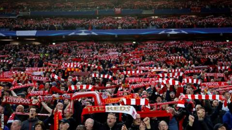 Liverpool fans hold aloft scarves at Anfield