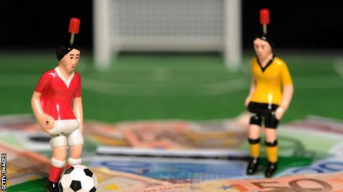Figurines of footballers standing on a pile of cash