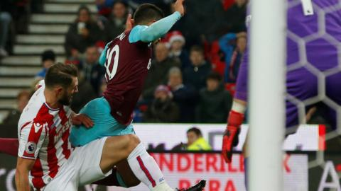 West Ham forward Manuel Lanzini falls over as he is tackled by Stoke defender Erik Pieters