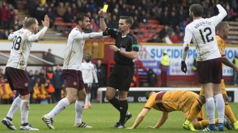 Hearts' Malaury Martin (left) is shown a yellow card from Andrew Dallas