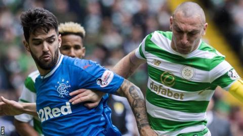 Daniel Candeias of Rangers and Celtic captain Scott Brown vie for posseesion