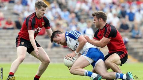 Monaghan's Shane Carey is tackled by Down's Conor Maginn and Gerard Collins