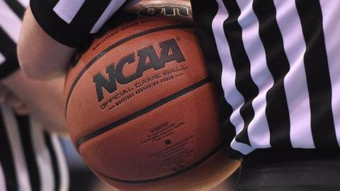 An official holds the ball during a US college basketball game
