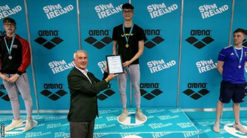 Jack McMillan receives his gold medal and record certificate from Swim Ireland president Declan Harte