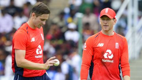 England captain Eoin Morgan (R) speaks with team-mate Chris Woakes