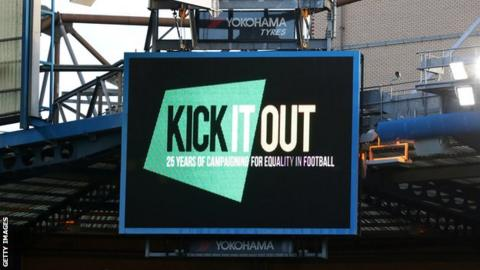 The Kick It Out logo on a screen in a football stadium
