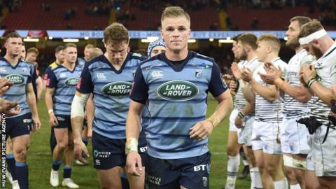 Gareth Anscombe walks through a tunnel of Ospreys players