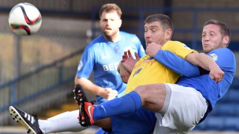 Ballymena United striker Matthew Tipton attempts to shield the ball from Glenavon defender Kris Lindsay