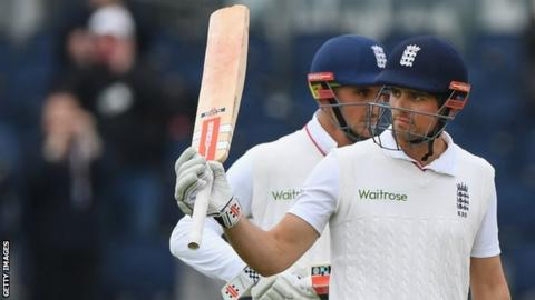 Alastair Cook raises his bat after reaching 10,000 Test runs