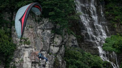 Zhangjiajie, China, 26 June: Boris Tysebaert, of France, takes part in the Heaven's Gate Paramotor Air Games, racing competitors from Spain, the USA, Brazil and Greece against the stunning backdrop of Tianmen Mountain. (Photo by Wang He/Getty Images)