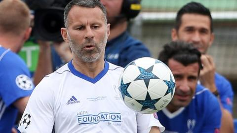 Ryan Giggs concentrates hard as he controls the ball during a charity football match