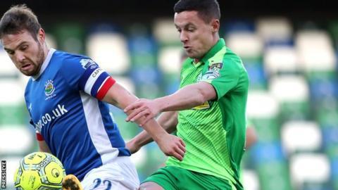 Linfield midfielder Jamie Mulgrew is challenged by Ruairi Harkin at Windsor Park