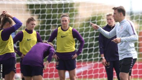 Phil Neville talks to his England players in training