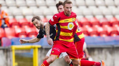 Partick Thistle's Ryan Stevenson fends off Dundee's Kevin Thomson