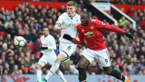 Swansea defender Alfie Mawson holds off Romelu Lukaku of Manchester United