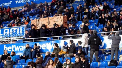 Alaves supporters dressed in black carrying a mock coffin in protest during their game against Levante