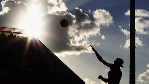 Chris Gregory of England serves against Dimitris Apostolou and Georgios Chrysostomou of Cyprus during the men's beach volleyball preliminary round