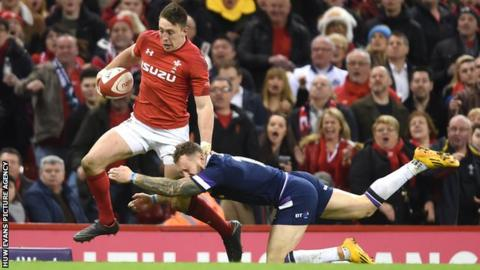 Josh Adams of Wales is tackled by Byron McGuigan of Scotland