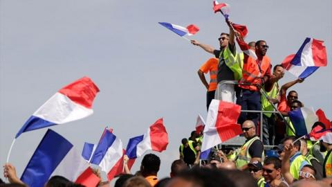 French fans wave flags as they wait for the arrival of the national football team at the Roissy-Charles de Gaulle airport on the outskirts of Paris, on 16 July 2018