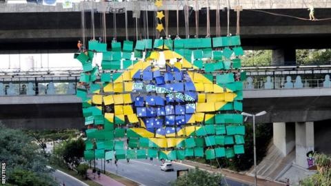 The Brazil flag created by climbers hangs off a motorway in Sao Paolo
