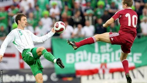 NI defender Jonny Evans challenges Latvia's Andrejs Rubins in the Euro 2008 qualifier in Riga