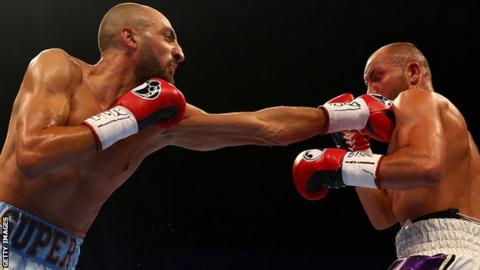 Evans in action against Bradley Skeete, in this image he is being punched in the face by a left jab