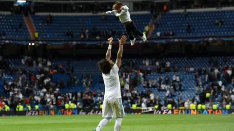 Marcelo of Real Madrid lifts his child into the air