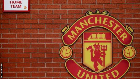 A wall with the Manchester United crest on it outside Old Trafford