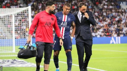 Kylian Mbappe hobbles from the field after getting injured playing for Paris St-Germain