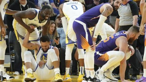 Golden State Warriors guard Stephen Curry was injured driving for the net in the third quarter against Phoenix Suns