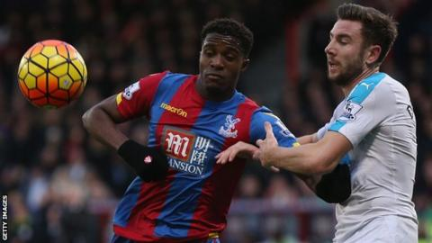 Wilfried Zaha of Crystal Palace and Paul Dummett of Newcastle in action