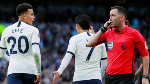 Referee Chris Kavanagh speaks with the Video Assistant Referee during Tottenham's match against Watford