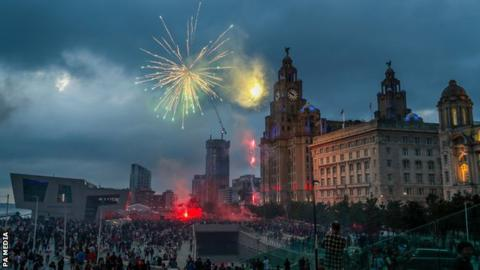 Fireworks are set off as crowds of Liverpool fans gather outside the Liver Building to celebrate the club's first Premier League title