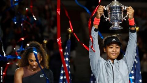 Naomi Osaka lifts US Open trophy as Serena Williams looks at the floor in the background