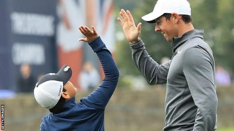 A young fan celebrates with Rory McIlroy after holing a putt in Wednesday's British Masters Pro-Am