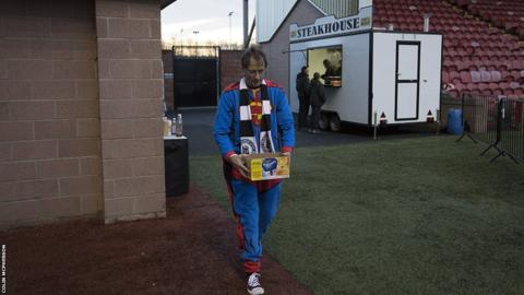 An Edinburgh City fan dressed as Superman with some half-time refreshments.