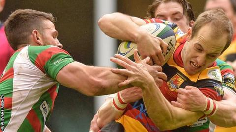Carmarthen Quins' Lee Williams is tackled by Rhodri Jones and Rhodri Davies of Llandovery